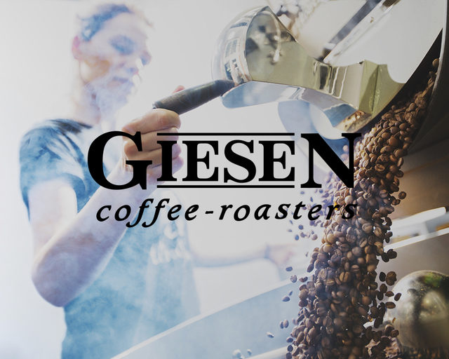 A woman operating a Giesen roaster